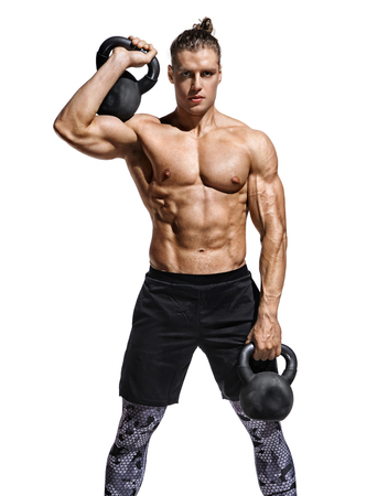Bodybuilder doing exercise with heavy weight kettlebells. Photo of muscular man with naked torso and good physique on white background. Strength and motivation Stock Photo