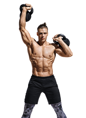 Sporty man training with kettlebells. Photo of sporty model with naked torso and good physique on white background. Strength and motivation