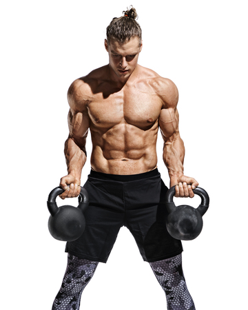 Strong man doing exercises with kettlebells at biceps. Photo of young man with good physique isolated on white background. Strength and motivation. Stock Photo