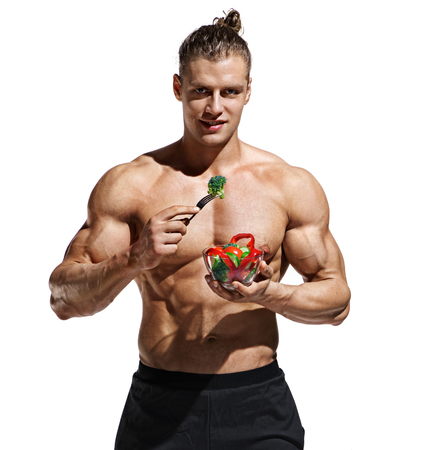 Athletic young man with bowl of salad. Photo of man eating healthy food on white background. Organic food and health concept
