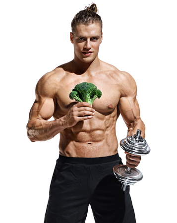 Sporty man holding broccoli and dumbbell as symbol healthy lifestyle. Photo of muscular man with naked torso and good physique on white background. Healthy lifestyle