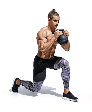 Sportive man workout with kettlebell doing lunges. Photo of young man with good physique isolated on white background. Strength and motivation.