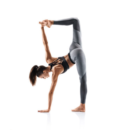 Sporty young woman doing yoga practice isolated on white background. Concept of healthy life and natural balance between body and mental development. Full length Reklamní fotografie
