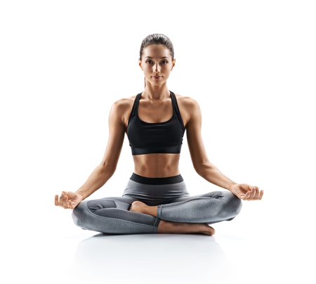 Sporty young woman doing yoga practice isolated on white background. Concept of healthy life and natural balance between body and mental development. Full length Stockfoto