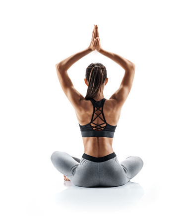 Young attractive girl practicing yoga isolated on white background. Concept of healthy life and natural balance between body and mental development. Full length Stock Photo