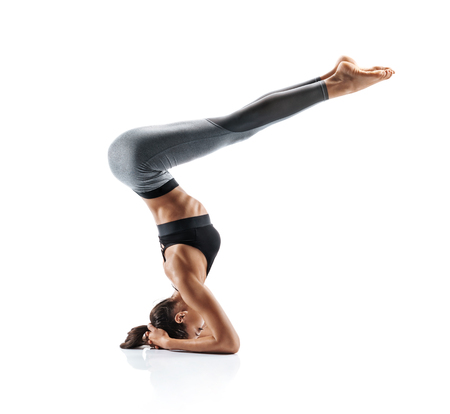 Silhouette of slim girl practicing yoga isolated on white background. Concept of healthy life and natural balance between body and mental development. Full length Stock Photo