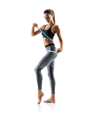 Young slim girl in sportswear isolated on white background. Concept of healthy life and natural balance between body and mental development. Full length