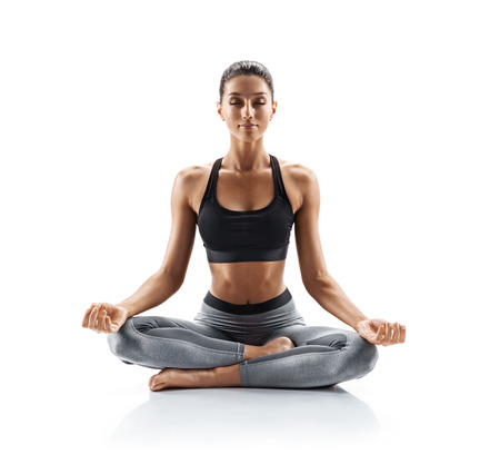 Sporty young woman doing yoga practice isolated on white background. Concept of healthy life and natural balance between body and mental development. Full length 版權商用圖片
