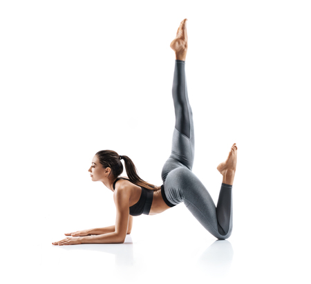 Beautiful young girl doing yoga or pilates exercise isolated on white background. Concept of healthy life and natural balance between body and mental development. Full length