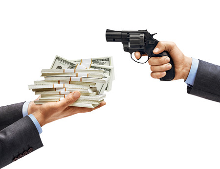 Mans hands holding bundles of money opposite mans hand with gun isolated on white background. Business concept. Close up. High resolution product