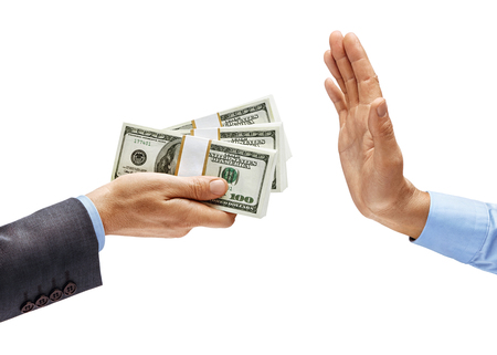 Mans hand in suit giving bundles of money and mans hand in shirt showing stop sign isolated on white background. Business concept. Close up. High resolution product Stock Photo