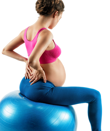Lower back pain. Photo of pregnant woman holding her back in pain isolated on white background. Stock Photo