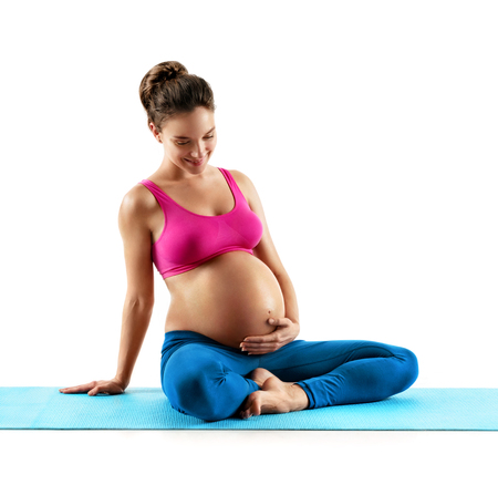 Smiling pregnant woman in sportswear sitting on mat and touching her belly isolated on white background. Stock Photo