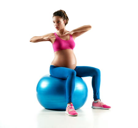 Pregnant woman exercising on fitball isolated on white background. Concept of healthy life