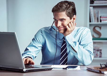 Manager man talking on the phone and looks at laptop. Photo of successful manager working with financial data in the office. Business concept