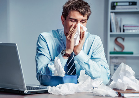 Sick worker blow his nose in paper tissues. Photo of young man working in the office. Business concept. 스톡 콘텐츠