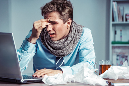 Young office man with pain in his head or an eye. Photo of sick man suffering from stress or a headache grimacing in pain. Business concept Reklamní fotografie