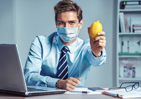 Healthy worker at the office holding lemon. Photo of man wearing protective mask against infectious diseases and flu. Business and health care concept. Reklamní fotografie