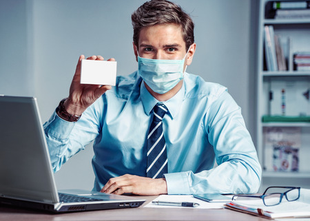 Healthy worker at the office holding white box of medicine. Photo of man wearing protective mask against infectious diseases and flu. Business and health care concept. Reklamní fotografie