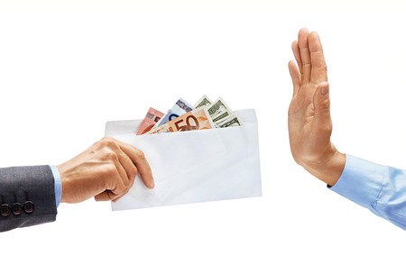 Mans hand in  giving full envelope of money and mans hand in shirt showing stop sign isolated on white background. High resolution product. Close up