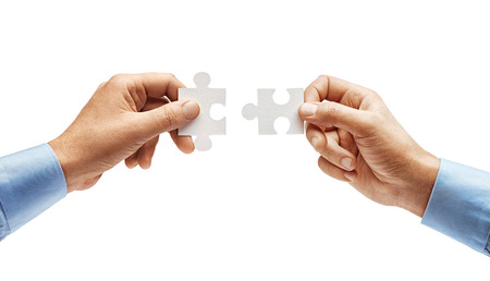 Two mens hands in shirt connecting jigsaw puzzle isolated on white background. Close up. High resolution product Reklamní fotografie