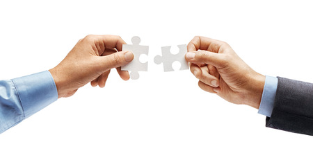 Mans hand in shirt and mans hand in suit trying to connect puzzle pieces isolated on white background. Close up. High resolution product