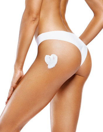Applying moisturizer cream. Slim girl in white lingerie cares about her buttocks. Beauty part of female body isolated on white background. Skin care concept