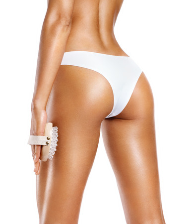 Woman using anti-cellulite massager. Photo of tanned slim body isolated on white background. Body care concept 写真素材 - 109073605