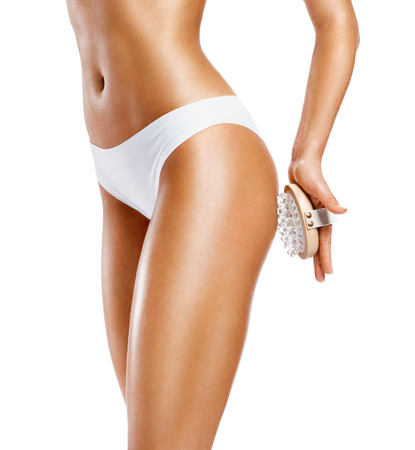 Woman using anti-cellulite massager. Photo of tanned slim body isolated on white background. Body care concept