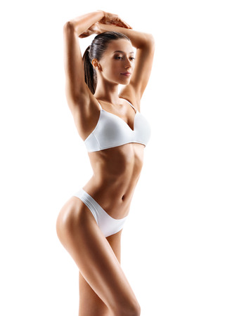 Slim tanned womans body. Photo of perfect body in white lingerie on white background. Beauty and body care concept Reklamní fotografie