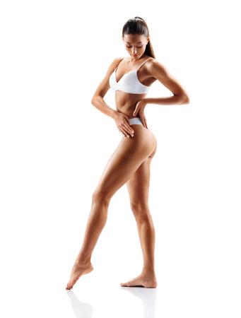 Slim tanned girl in white lingerie posing on white background. Beauty and body care concept Reklamní fotografie