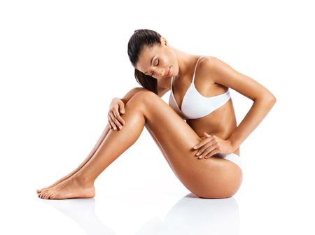 Young girl with perfect body touching her leg sitting on white background. Beauty & Skin care concept Reklamní fotografie