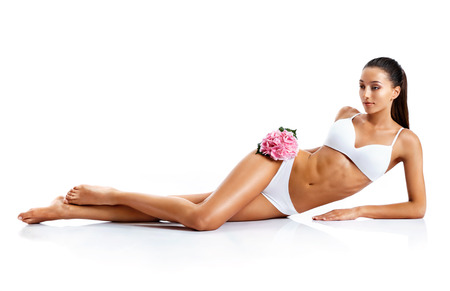 Young woman with beautiful long legs. Photo of tanned womans body isolated on white background. Beauty & Skin care concept.