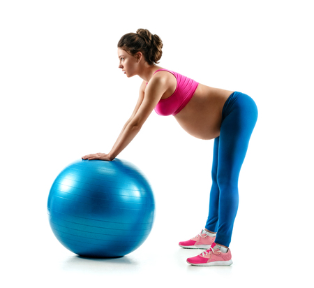 Pregnant woman exercising on gymnastic ball isolated on white background. Concept of healthy life Reklamní fotografie