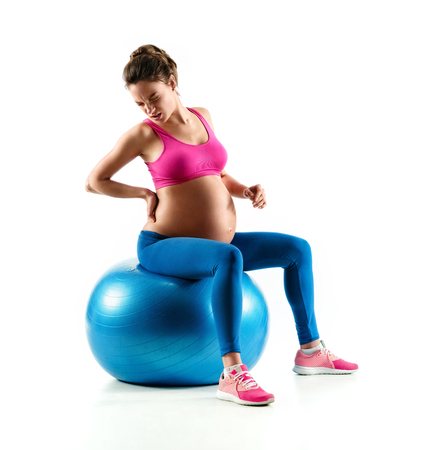 Lower back pain. Photo of pregnant woman holding her back in pain isolated on white background. Concept of healthy life Reklamní fotografie