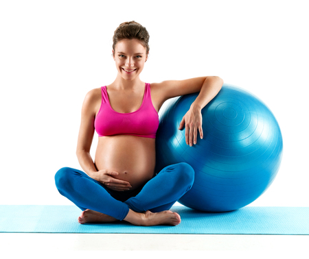 Smiling pregnant woman sitting with fit ball isolated on white background. Concept of healthy life Reklamní fotografie