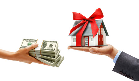 Womans hand giving bundles of money and mans hand in suit holding house with red ribbon isolated on white background. Close up. High resolution product