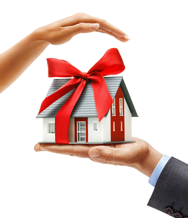 Mans hand in suit holding new house with red ribbon and womans hand above cares about house isolated on white background. Close up. High resolution product