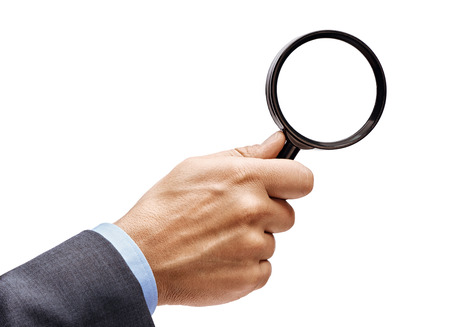 Mans hand in suit holding magnifying glass isolated on white background. Close up. High resolution product