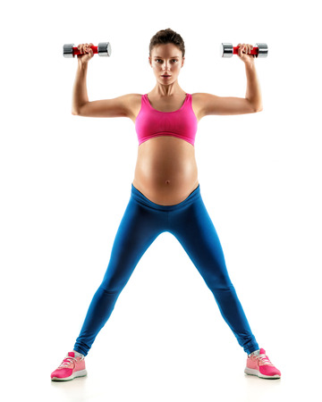 Sporty pregnant woman doing exercises with dumbbells isolated on white background. Concept of healthy life Stock Photo