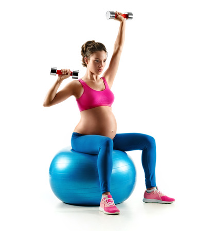 Pregnant woman exercising on gymnastic ball with dumbbells isolated on white background. Concept of healthy life