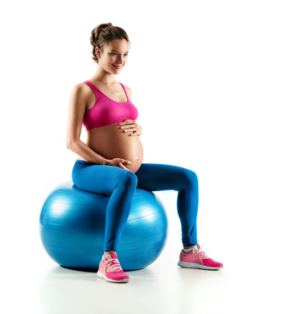 Smiling pregnant woman in sportswear sitting on fit ball and touching her belly isolated on white background. Concept of healthy life
