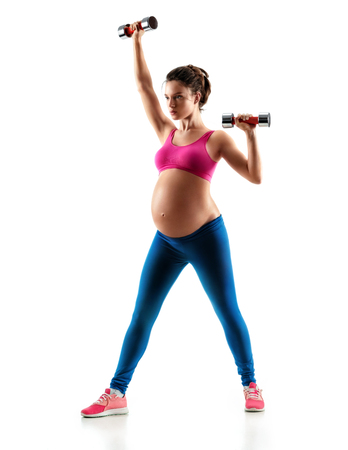 Sporty pregnant woman training muscles of hands using a dumbbells isolated on white background. Concept of healthy life