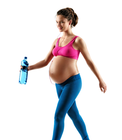 Sporty pregnant woman in sportswear jogging on white background. Dynamic movement. Concept of healthy life Stock Photo