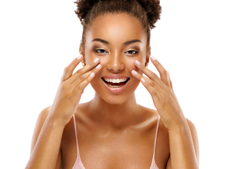 Beautiful woman doing facial massage, touching her face. Photo of african woman with clean healthy skin on white background. Skin care and beauty concept 写真素材