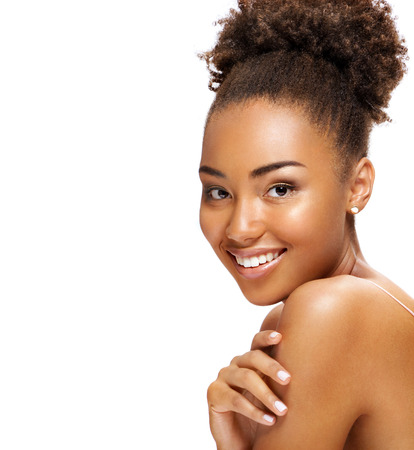 Young girl touching her healthy skin. Photo of smiling african american girl on white background. Youth and skin care concept