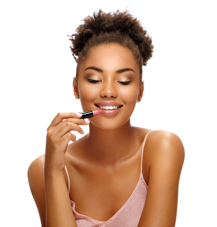 Beautiful girl applying lipstick on her lips. Photo of african american girl with perfect makeup on white background. Skin care and beauty