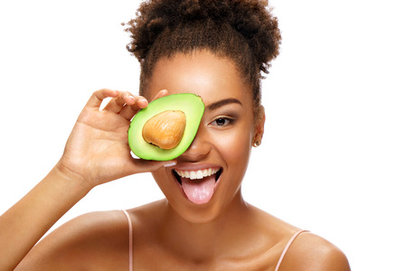 Funny girl holding half an avocado in front of her face and showing tongue. Photo of smiling african american woman on white background. Beauty & Skin care concept