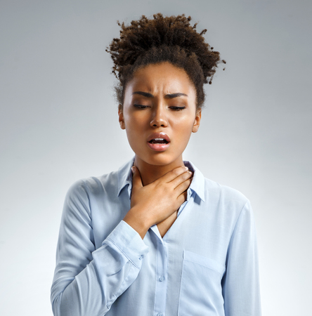 Throat pain. Woman holding her inflamed throat. Photo of african american woman in blue shirt on gray background. Medical concept
