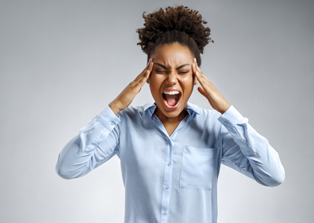 Woman suffering from stress or a headache grimacing in pain. Photo of african american woman in blue shirt on gray background. Medical concept.